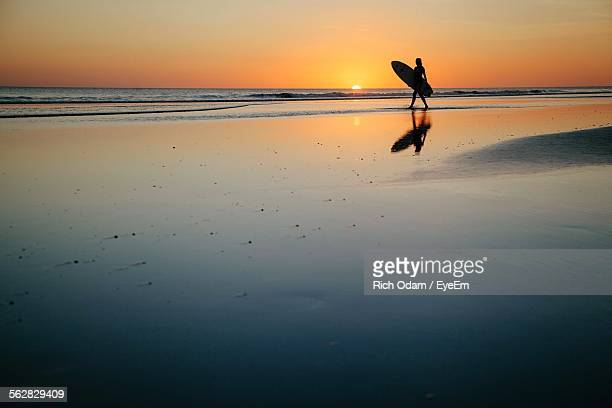 Silhouette Woman With Surfboard Walking On Shore During Sunset