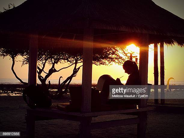 Silhouette Woman Writing While Sitting Under Gazebo By Sea Against Sky During Sunset