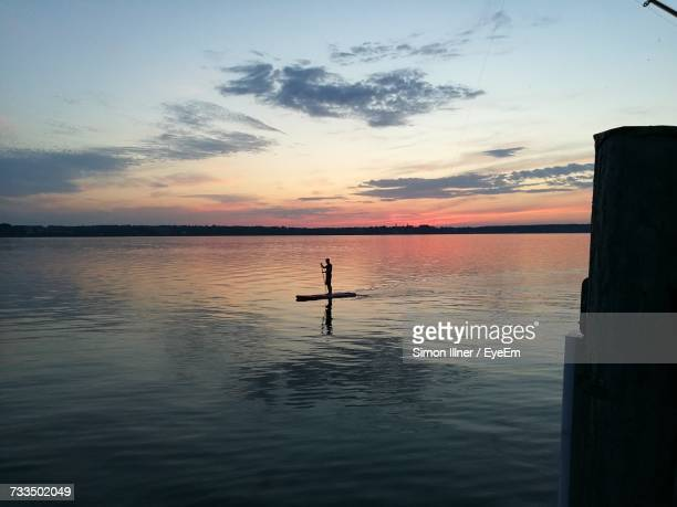 Silhouette Wooden Post In Sea Against Sky During Sunset