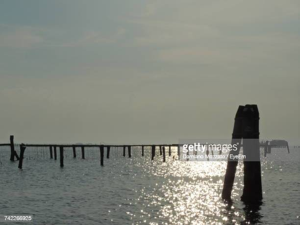 Silhouette Wooden Posts In Sea Against Sky