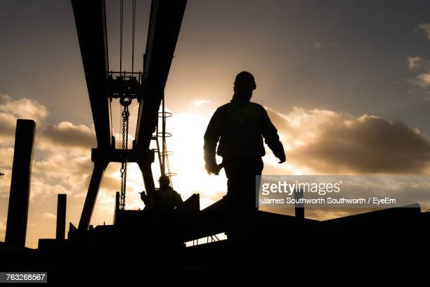 Silhouette Worker By Metallic Structure Against Cloudy Sky During Sunset