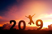 Silhouette young woman jumping to 2019 new year