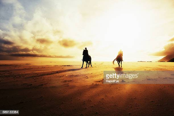 Silhouetted against setting sun, horseback riders throw shadows on sand