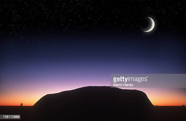 Silhouetted Ayers Rock at sunrise with crescent moon, Kata Tjutu National Park. Australia. (Digital Composite)