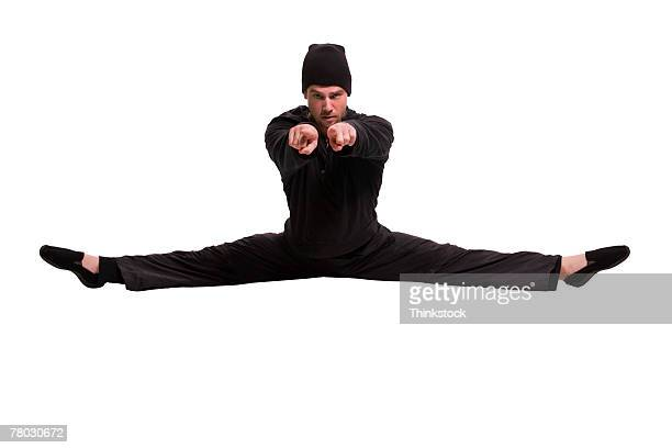 Silhouetted breakdancer doing a split and pointing to the viewer