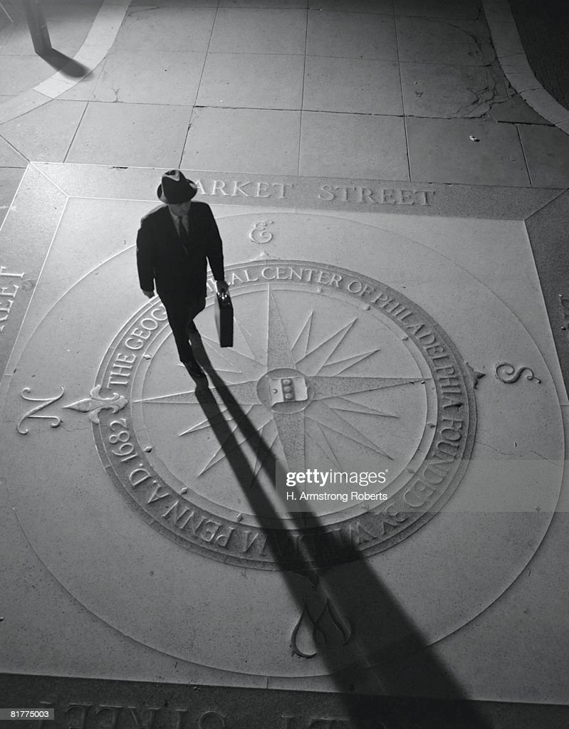 Silhouetted businessman with briefcase walking across compass in the sidewalk, elevated view, Philadelphia. : Stock Photo