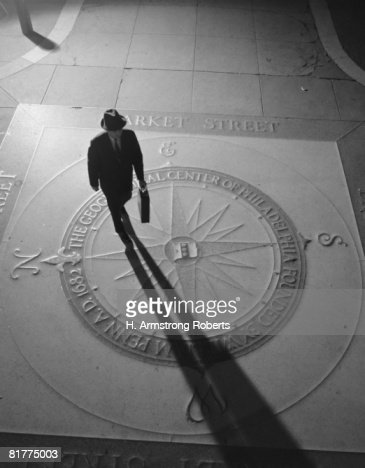Silhouetted businessman with briefcase walking across compass in the sidewalk, elevated view, Philadelphia. : Bildbanksbilder