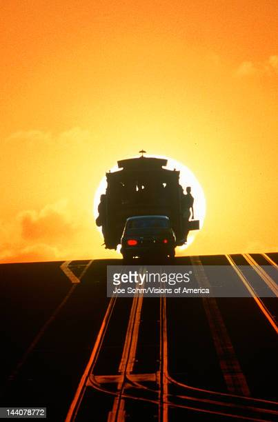 Silhouetted cable car going over hill at sunset in San Francisco California