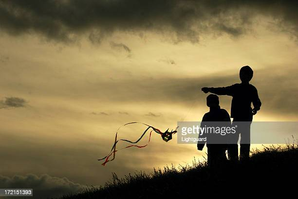 Silhouetted children flying a colorful kite at sundown
