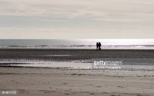Silhouetted Couple Walking on a Bench