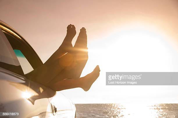 Silhouetted feet out of car window at sunset, Miami, Florida, USA