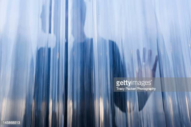 Silhouetted figure behind transparent screen