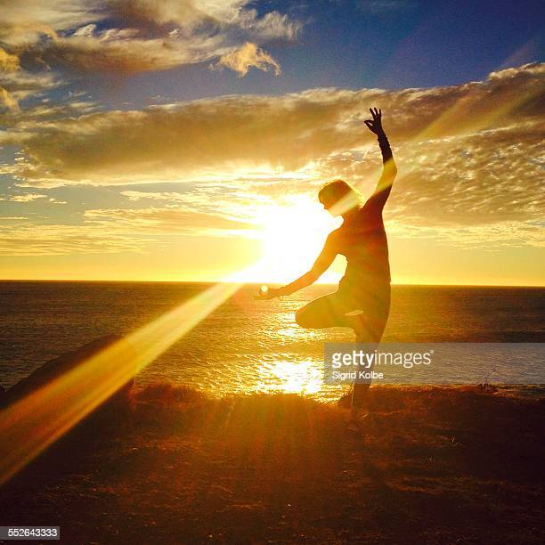 A silhouetted figure of a woman in a tree pose variation with sunflare