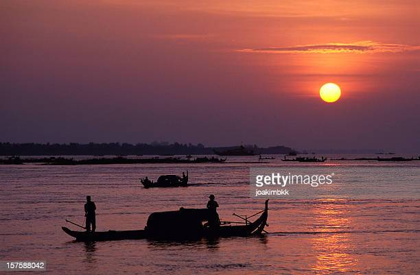 Silhouetted fishermen at sunrise on the Mekong River