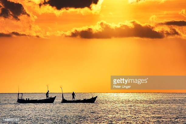 Silhouetted fishing boats at sunset.