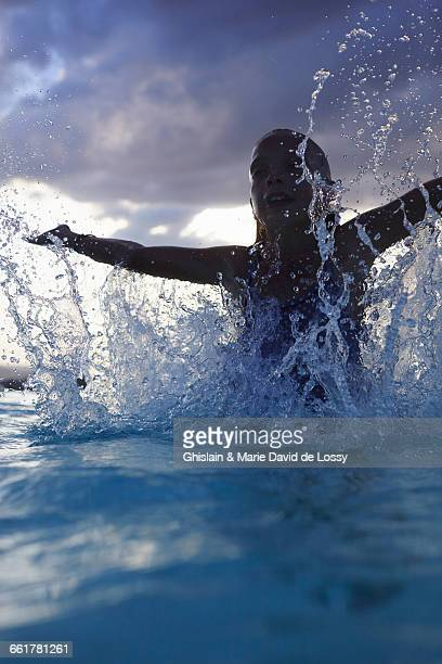 Silhouetted girl splashing in swimming pool, Buonconvento, Tuscany, Italy