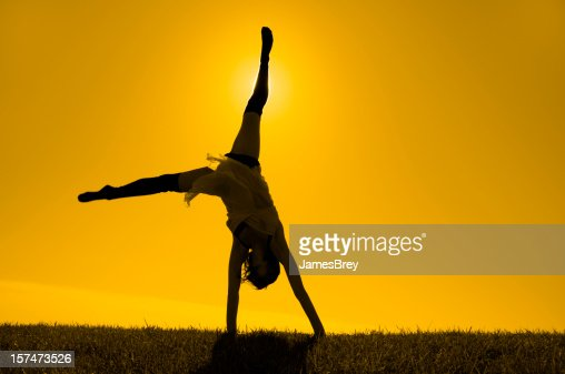 Silhouetted Girl Turning Cartwheels on Horizon In Yellow Gold Sunlight