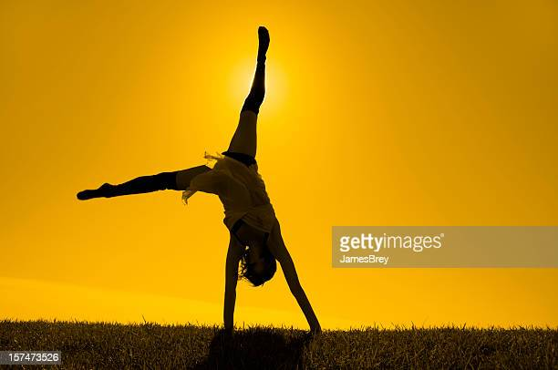Silhouetted Girl Turning Cartwheels on Horizon In Yellow Gold Sunlight