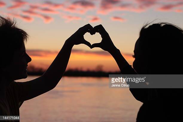 Silhouetted heart with hands against sunset