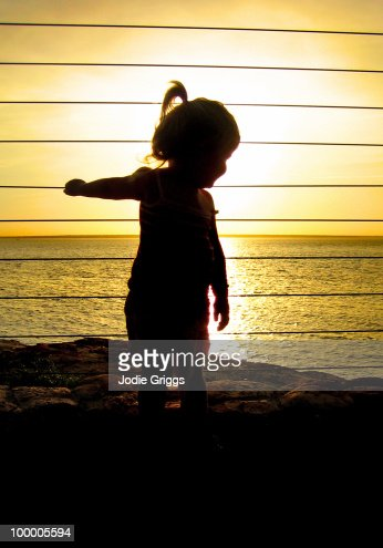Silhouetted image of child at sunset : Stock Photo