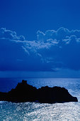 Silhouetted island in sea