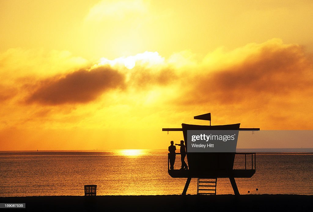 Silhouetted life guards watching the sun rise : Stock Photo