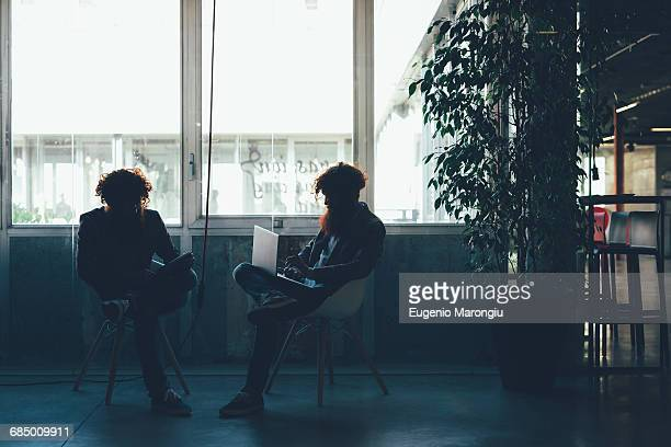 Silhouetted male hipster twins working on laptop and digital tablet in office