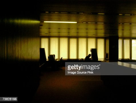 Silhouetted man in office : Stock Photo