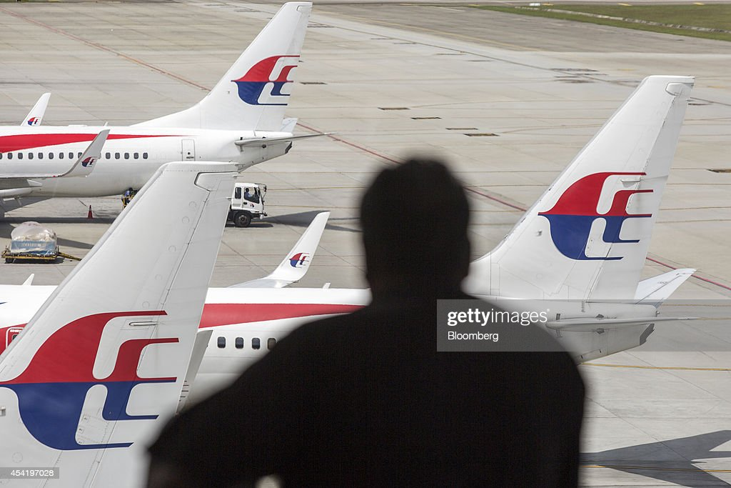 A silhouetted man looks out at aircraft operated by Malaysian Airline System Bhd. (MAS) standing on the tarmac at Kuala Lumpur International Airport (KLIA) in Sepang, Malaysia, on Tuesday, Aug. 26, 2014. Malaysia Airlines are scheduled to release second quarter earnings Aug. 27 as the airline considers job cuts, a review of aircraft orders and replacing its chief executive officer after the national carrier suffered two disasters this year, people familiar with the plan said. Photographer: Charles Pertwee/Bloomberg via Getty Images