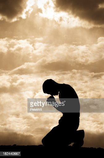 Silhouetted man on his knees praying