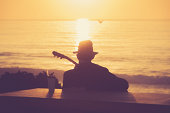 Silhouetted Man Playing Guitar at Sunset