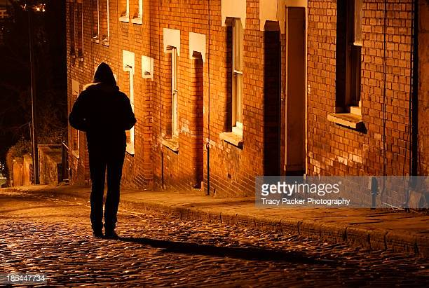 Silhouetted man stands outside a terrace at night.