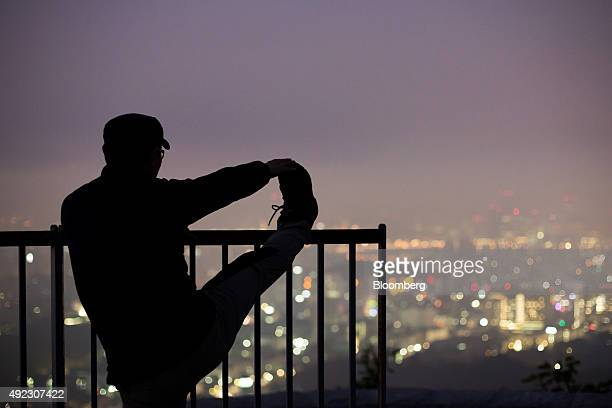 A silhouetted man stretches as he looks out at the city skyline shrouded in haze from the observation deck of Ansan mountain at dawn in Seoul South...
