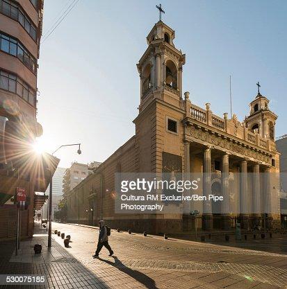 Silhouetted man walking near Templo San Agustin at sunrise, Santiago, Chile