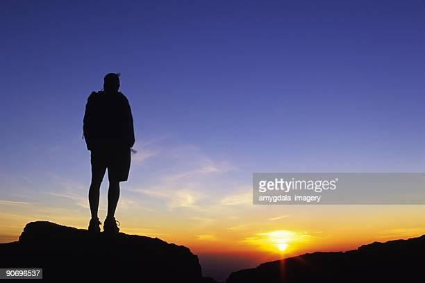 シルエットの男性ながら、日の出を眺めるスカイ