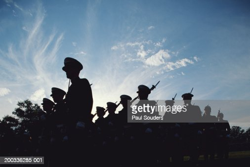 Silhouetted naval cadets marching in formation, low angle view : Stock Photo