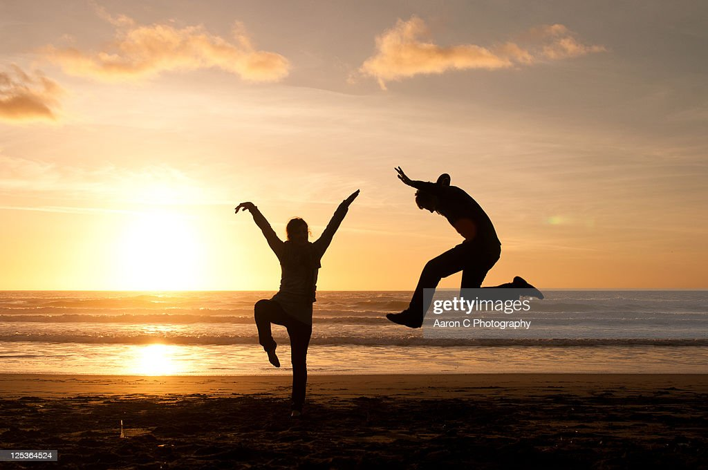 Silhouetted of two people  on California beach : Stock Photo