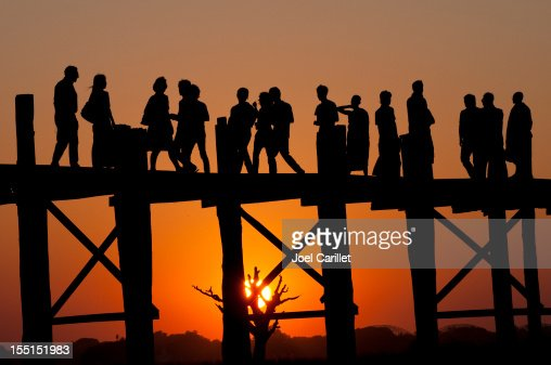 Silhouetted people together at sunset on U Bein Bridge