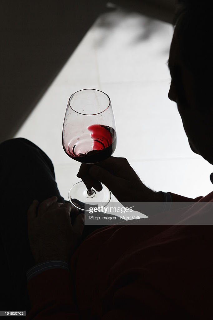 A silhouetted person swirling wine in a wineglass
