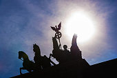 Silhouetted quadriga statue with sunset, Brandenburg Gate in Berlin