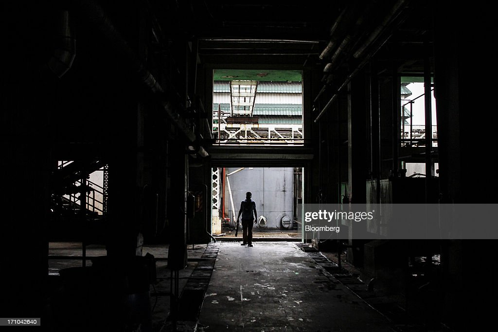 A silhouetted Ruchi Soya Industries Ltd. employee walks through an industrial building at the company's edible oil refinery plant in Patalganga, India, on Tuesday, June 18, 2013. Monsoon, which accounts for 70 percent of Indias annual rainfall, covered the entire country in a record time, accelerating plantings of crops from rice to soybeans and cotton. Rains covered the whole of India by June 16, the earliest ever and ahead of the normal date of July 15, said D.S. Pai, head of the long-range forecasting division at the India Meteorological Department. Photographer: Dhiraj Singh/Bloomberg via Getty Images