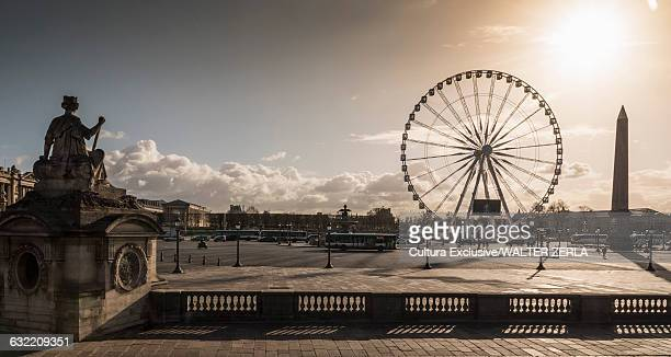 Silhouetted statue and Grande Roue ferris wheel at dusk, Paris, France