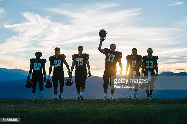 Silhouetted teenage and young male american football team celebrating at dusk