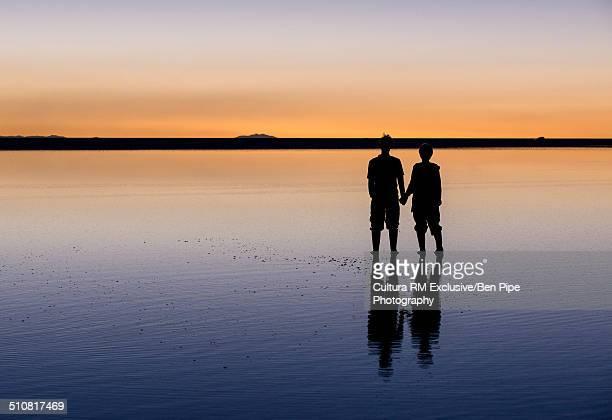 Silhouetted tousrists on salt flats at dusk, Salar de Uyuni, Southern Altiplano, Bolivia, South America