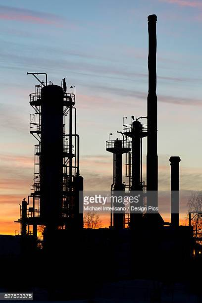 Silhouetted towers of a gas plant at sunset with orange cast clouds and blue sky