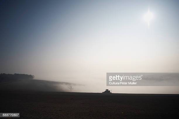 Silhouetted tractor ploughing field in morning mist