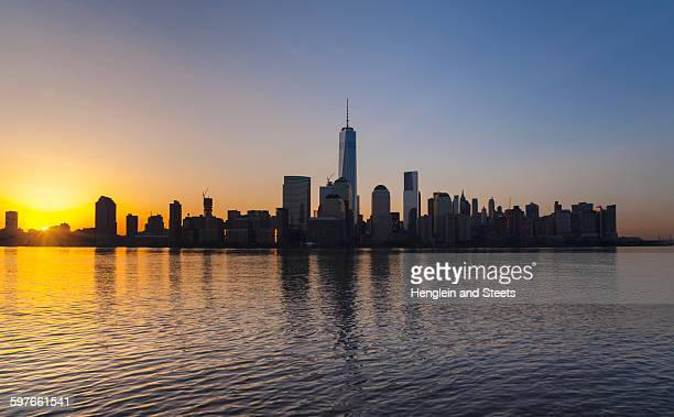 Silhouetted view of Manhattan financial district skyline at sunset, New York, USA