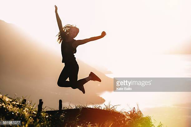Silhouetted view of young woman jumping mid air at sunset above Lake Atitlan, Guatemala