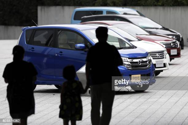Silhouetted visitors walk towards Nissan Motor Co vehicles including a Dayz Highway Star vehicle front on display outside the company's showroom in...
