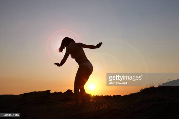 Silhouetted woman dancing in sunset